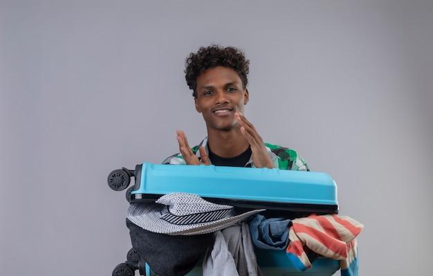 Jonge afro-amerikaanse reiziger man die met koffer vol kleren kijken camera applaudisseren glimlachend vriendelijk op witte achtergrond