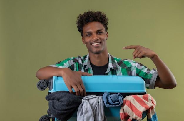 Jonge afro-amerikaanse reiziger man die met koffer vol kleren kijken camera blij en positief glimlachend wijzend met vinger naar de zijkant over groene achtergrond
