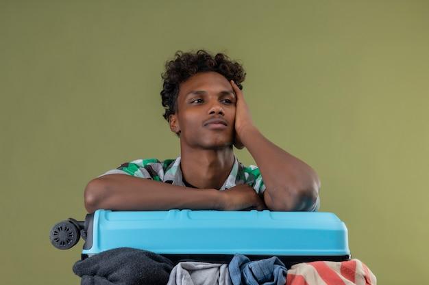 Jonge afro-amerikaanse reiziger man die met koffer vol kleren opzij kijken met peinzende uitdrukking positief denken over groene achtergrond