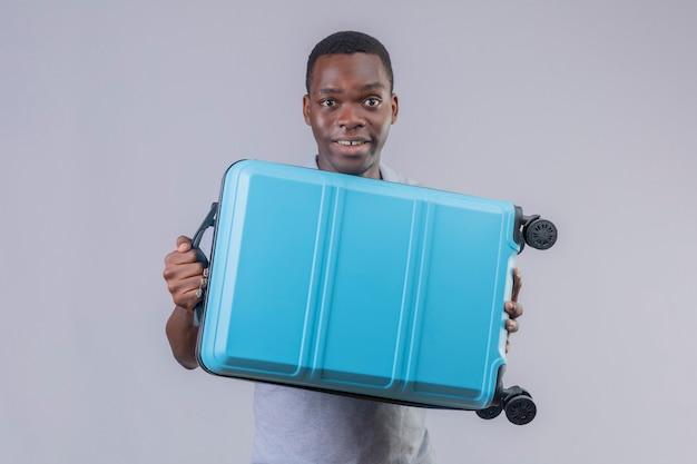 Jonge afro-amerikaanse reiziger man in grijs poloshirt met blauwe koffer op zoek verrast en blij