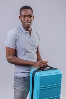 Jonge afro-amerikaanse reiziger man in grijs poloshirt met blauwe koffer positief en gelukkig lachend