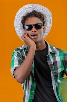 Jonge afro-amerikaanse reiziger man in zomer hoed dragen zwarte zonnebril houden opblaasbare ring verbaasd en verbaasd kijken naar camera staande over oranje achtergrond