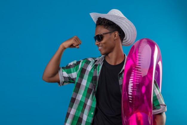 Jonge afro-amerikaanse reiziger man in zomer hoed dragen zwarte zonnebril permanent met koffer bedrijf opblaasbare ring verhogen vuist tonen biceps glimlachend vrolijk winnaar concept over
