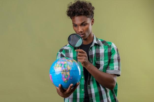 Jonge afro-amerikaanse reiziger man met globe kijken door vergrootglas verrast