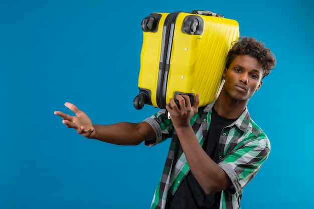 Jonge afro-amerikaanse reiziger man met koffer met uitdrukking op gezicht met opgeheven hand verwarren