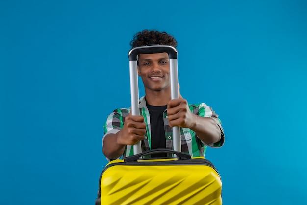 Jonge afro-amerikaanse reiziger man met koffer met zelfverzekerde glimlach con gezicht