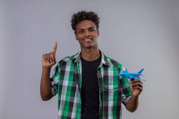 Jonge afro-amerikaanse reiziger man met speelgoed vliegtuig wijzende vinger omhoog lachend met zelfverzekerde uitdrukking op gezicht staande op witte achtergrond