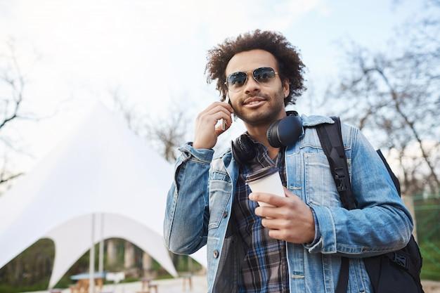 Jonge afro-amerikaanse reiziger met afro kapsel koffie te houden tijdens het wandelen en praten op smartphone, opzij kijken met gefocuste en tevreden uitdrukking.