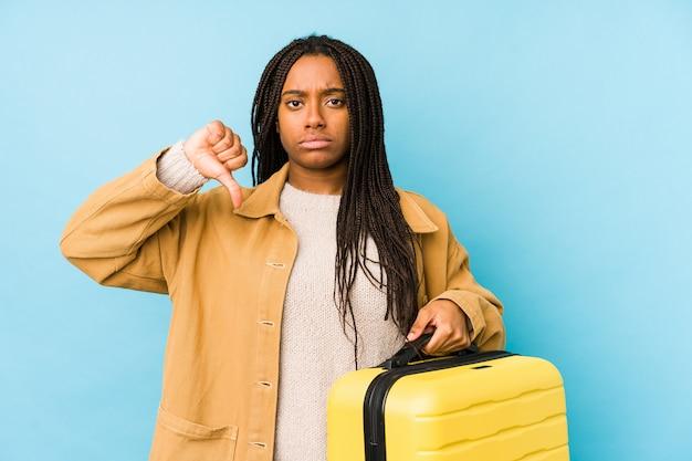 Jonge afro-amerikaanse reizigersvrouw die een geïsoleerde koffer houdt die een afkeergebaar toont, duim omlaag. meningsverschil concept.