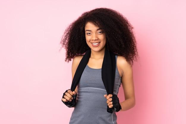 Jonge afro-amerikaanse sport vrouw geïsoleerd op roze met sporthanddoek
