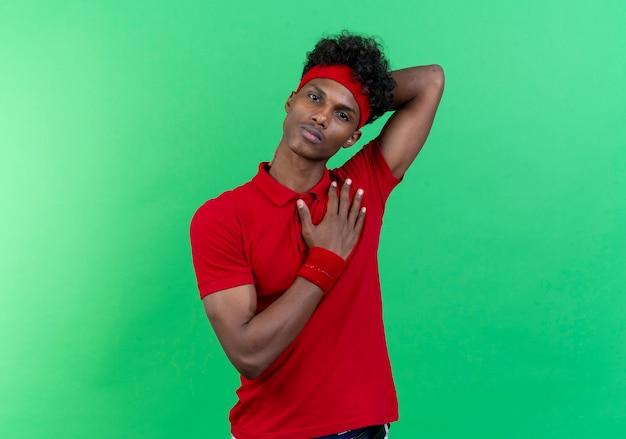 Jonge afro-amerikaanse sportieve man met hoofdband en polsband hand op hart en andere hand op nek geïsoleerd op groene muur