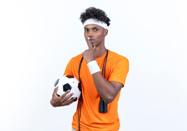 Jonge afro-amerikaanse sportieve man met hoofdband en polsbandje bedrijf bal weergegeven: stilte gebaar met springtouw op schouder