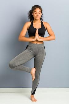 Jonge afro-amerikaanse sportieve vrouw het beoefenen van yoga