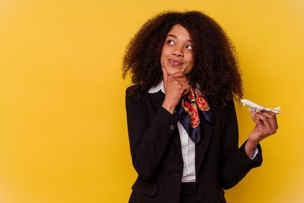 Jonge afro-amerikaanse stewardess die een klein vliegtuig houdt dat op geel wordt geïsoleerd en zijwaarts kijkt met twijfelachtige en sceptische uitdrukking.