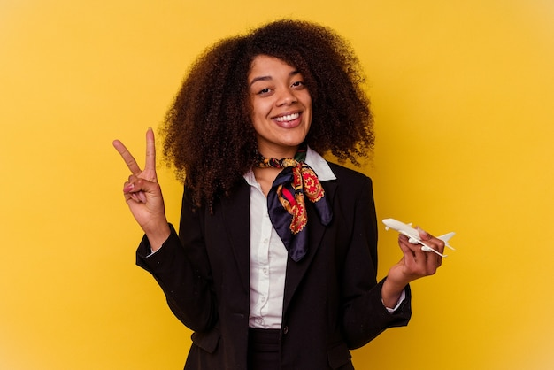 Jonge afro-amerikaanse stewardess die een klein vliegtuig houdt dat op gele achtergrond wordt geïsoleerd die nummer twee met vingers toont.