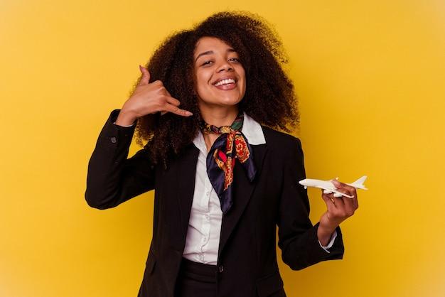 Jonge afro-amerikaanse stewardess die een klein vliegtuig houdt dat op gele muur wordt geïsoleerd en een mobiel telefoongesprekgebaar met vingers toont.