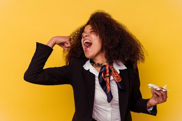 Jonge afro-amerikaanse stewardess die een vliegtuigje vasthoudt dat op een gele achtergrond wordt geïsoleerd en de vuist opheft na een overwinning, winnaarconcept.