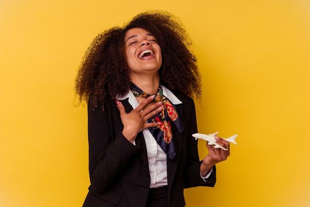 Jonge afro-amerikaanse stewardess die een vliegtuigje vasthoudt dat op geel wordt geïsoleerd, lacht hardop terwijl ze de hand op de borst houdt.