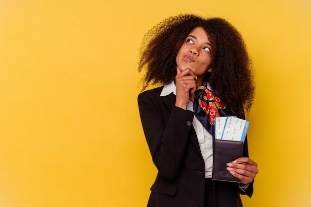 Jonge afro-amerikaanse stewardess die een vliegtuigkaartje houdt die op gele achtergrond worden geïsoleerd die zijwaarts met twijfelachtige en sceptische uitdrukking kijkt.