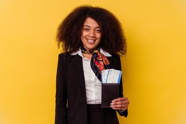 Jonge afro-amerikaanse stewardess die een vliegtuigkaartjes houdt die op geel gelukkig, glimlachend en vrolijk worden geïsoleerd.