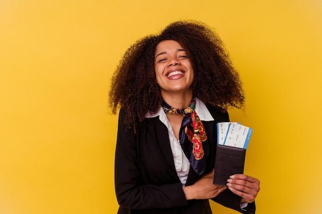 Jonge afro-amerikaanse stewardess die een vliegtuigkaartjes houdt die op geel worden geïsoleerd dat en pret lacht heeft.