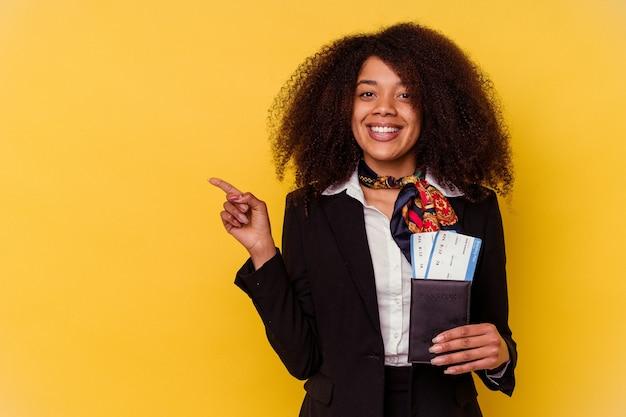 Jonge afro-amerikaanse stewardess die een vliegtuigkaartjes houdt die op geel worden geïsoleerd glimlachend en opzij wijzen, die iets op lege ruimte tonen.