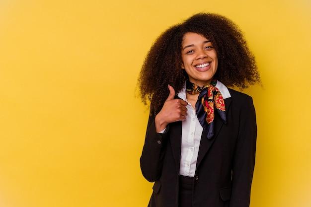 Jonge afro-amerikaanse stewardess geïsoleerd op geel glimlachend en duim omhoog