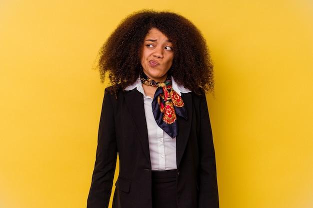 Jonge afro-amerikaanse stewardess geïsoleerd op geel in de war, voelt zich twijfelachtig en onzeker.