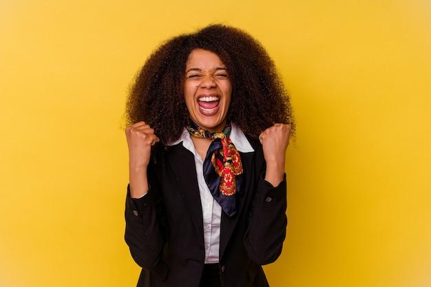 Jonge afro-amerikaanse stewardess geïsoleerd op geel onbezorgd en opgewonden toejuichen. overwinning concept.