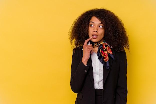 Jonge afro-amerikaanse stewardess geïsoleerd op geel zijwaarts kijkend met twijfelachtige en sceptische uitdrukking.