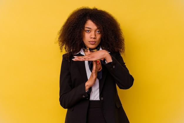 Jonge afro-amerikaanse stewardess geïsoleerd op gele achtergrond met een time-out gebaar.