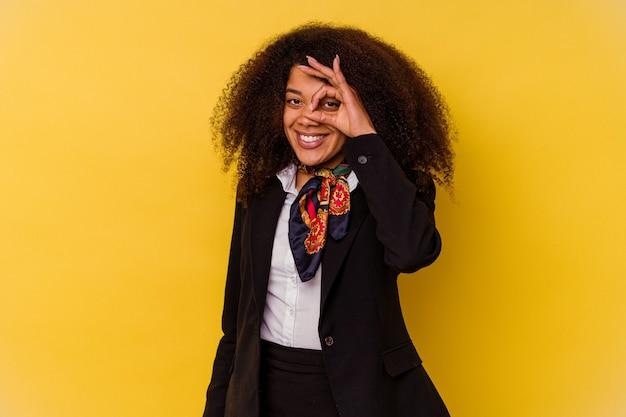 Jonge afro-amerikaanse stewardess geïsoleerd op gele achtergrond opgewonden houden ok gebaar op oog.