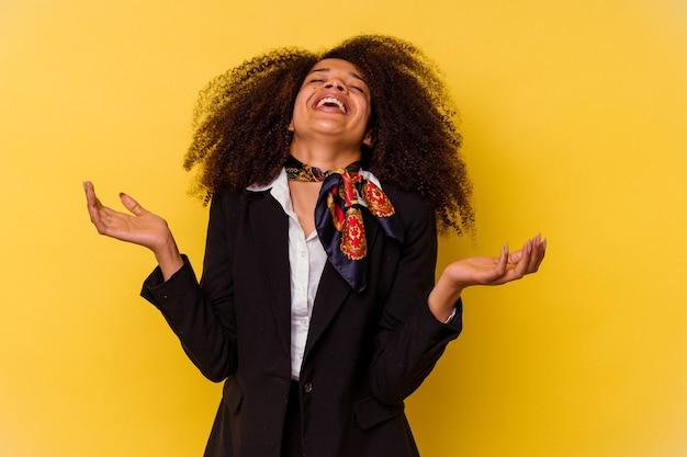 Jonge afro-amerikaanse stewardess geïsoleerd op gele achtergrond vrolijk veel lachen. geluk concept.