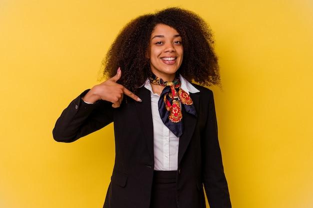 Jonge afro-amerikaanse stewardess geïsoleerd op gele persoon die met de hand wijst naar een ruimte voor een shirtkopie, trots en zelfverzekerd