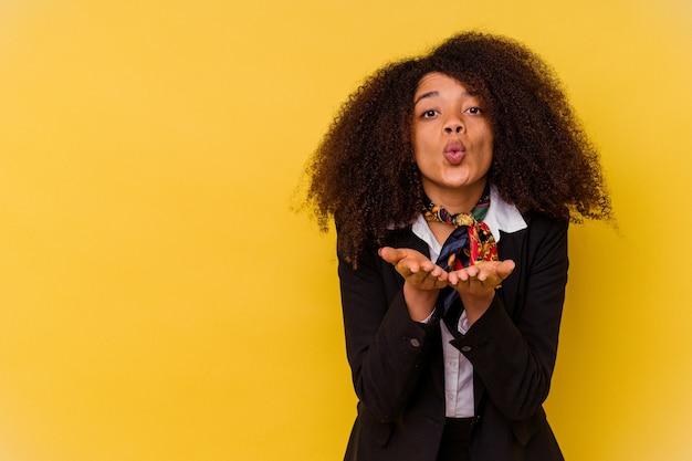 Jonge afro-amerikaanse stewardess geïsoleerd op gele vouwende lippen en handpalmen vasthoudend om luchtkus te sturen.