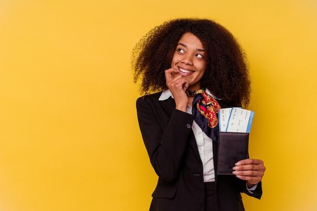 Jonge afro-amerikaanse stewardess met vliegtickets geïsoleerd op geel ontspannen denkend aan iets dat naar een kopieerruimte kijkt.
