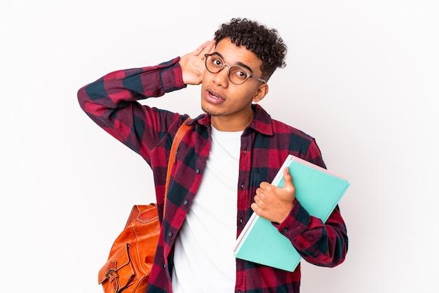 Jonge afro-amerikaanse student krullende man geïsoleerd bedrijf boeken proberen te luisteren een roddels.