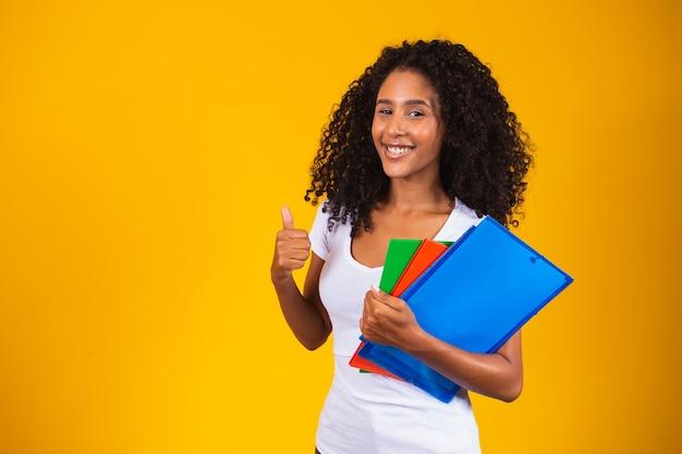 Jonge afro-amerikaanse student op gele achtergrond