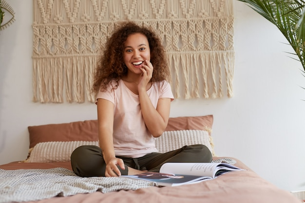 Jonge afro-amerikaanse verrast vrouw met krullend haar, zit op het bed en raakt de wang, glimlacht breed en leest een nieuw tijdschrift, geniet van cool nieuws in een tijdschrift, cool brengt vrije tijd thuis door.