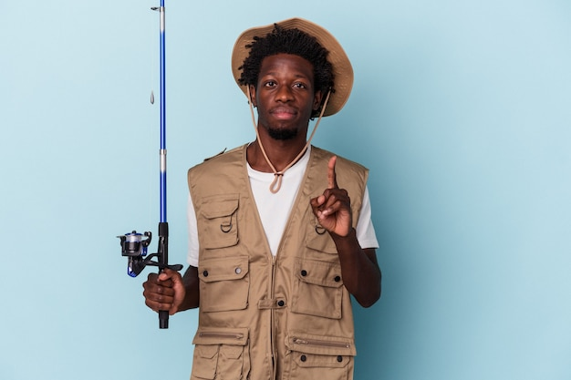 Jonge afro-amerikaanse visser die een staaf houdt die op blauwe achtergrond wordt geïsoleerd die nummer één met vinger toont.