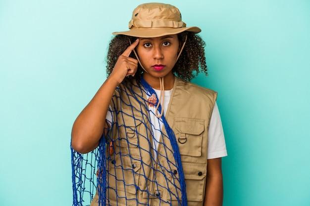 Jonge afro-amerikaanse vissersvrouw met net geïsoleerd op blauwe achtergrond wijzende tempel met vinger, denken, gericht op een taak.