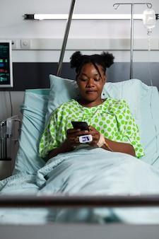 Jonge afro-amerikaanse volwassene zittend in ziekenhuisbed met smartphone voor websurfen en communicatie. tienerpatiënt die op medicijnen en overleg wacht terwijl hij een online gadget heeft