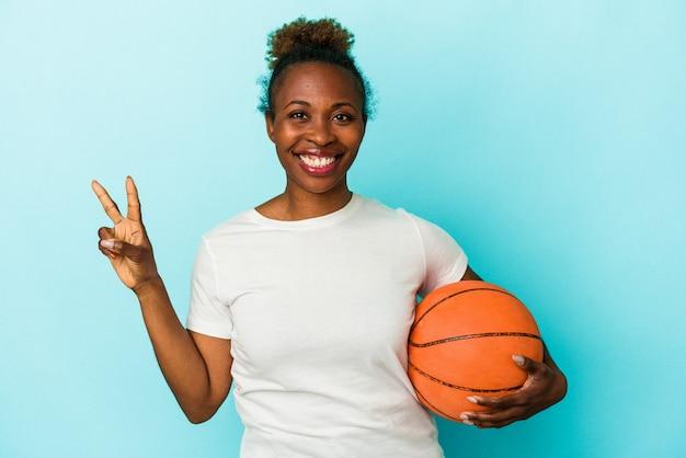 Jonge afro-amerikaanse vrouw die basketbal speelt geïsoleerd op een blauwe achtergrond met nummer twee met vingers.