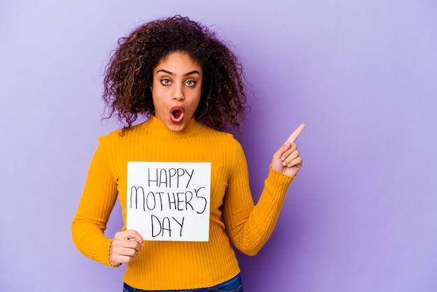 Jonge afro-amerikaanse vrouw die een aanplakbiljet van de gelukkige moederdag geïsoleerd houdt wijzend naar de kant