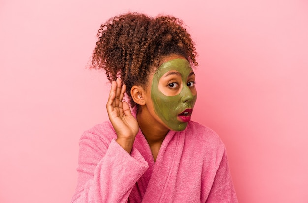 Jonge afro-amerikaanse vrouw die een badjas en een gezichtsmasker draagt dat op roze achtergrond wordt geïsoleerd en een roddel probeert te luisteren.
