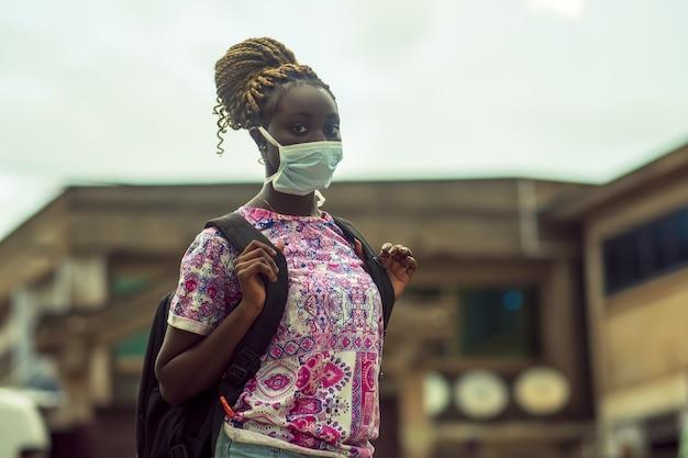 Jonge afro-amerikaanse vrouw die een beschermend gezichtsmasker draagt met een rugzak buitenshuis