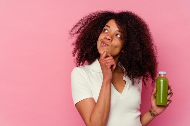 Jonge afro-amerikaanse vrouw die een gezonde smoothie drinkt geïsoleerd op roze zijwaarts kijkend met twijfelachtige en sceptische uitdrukking.