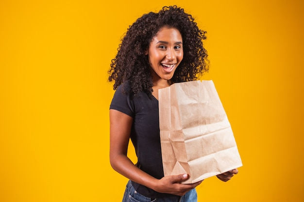 Jonge afro-amerikaanse vrouw die een papieren zak vasthoudt die gelukkig glimlacht op een gele achtergrond