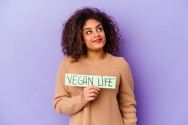 Jonge afro-amerikaanse vrouw die een plakkaat met veganistisch leven vasthoudt en droomt van het bereiken van doelen en doeleinden