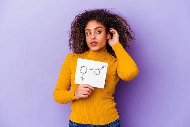 Jonge afro-amerikaanse vrouw die een plakkaat voor gendergelijkheid houdt dat op paars wordt geïsoleerd en probeert een roddel te luisteren.